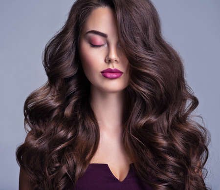 Photo pour Fashion model with wavy hairstyle. Attractive young  girl with curly hair posing at studio.  Face of a beautiful woman with long brown curly hair. Female face with purple makeup. Violet make-up. - image libre de droit