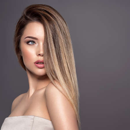 Photo pour Young woman with long straight hair. Sexy and gorgeous blonde woman. Portrait of an attractive female posing at studio. Closeup face of a beautiful girl with makeup smoky eyes. - image libre de droit