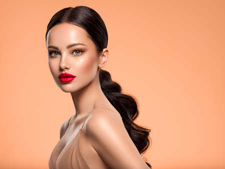 Foto de Beautiful white girl with a red lipstick on lips. Stunning brunette girl with long black hair. Closeup face of young beautiful woman with a healthy clean skin. Pretty woman with bright makeup - Imagen libre de derechos