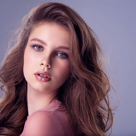 Foto de Beautiful brown-hair girl with long, wavy hair. Young model posing in the studio on a light blue background.  Attractive woman with makeup looking at the camera. Pretty caucasian girl with healthy skin. - Imagen libre de derechos