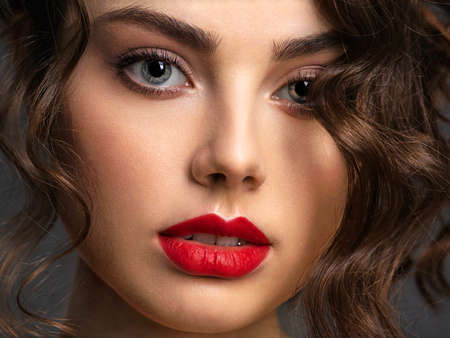 Photo pour Closeup Face of a beautiful woman with a smoky eye makeup and red lipstick. Sexy and gorgeous brunette girl  with long curly hair. Portrait of an attractive female -  at studio. Fashion model. - image libre de droit