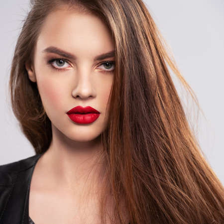 Photo pour Portrait of beautiful young woman with bright makeup. Beautiful brunette with bright red lipstick on her lips. Pretty girl with long brown hair. Brunette dressed in a black leather jacket. Sexy girl - image libre de droit