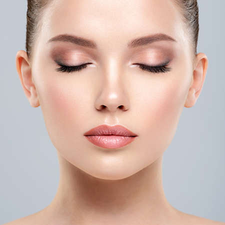 Photo pour Closeup portrait of a  face of the young pretty girl with a healthy skin. Calm  face of young white woman with a clean skin. Skin care concept. - image libre de droit