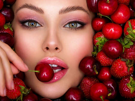 Photo pour Young girl with bright makeup and a berry background. Beautiful caucasian woman biting a berry. Attractive woman tasting cherry. Beautiful woman with fashion makeup and a vivid background. - image libre de droit