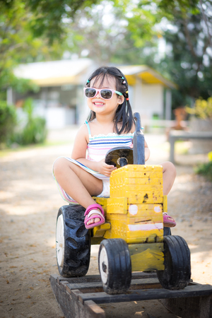 Photo pour Cute asian little girl wear sunglasses playing by driving a old tractor in farm - image libre de droit