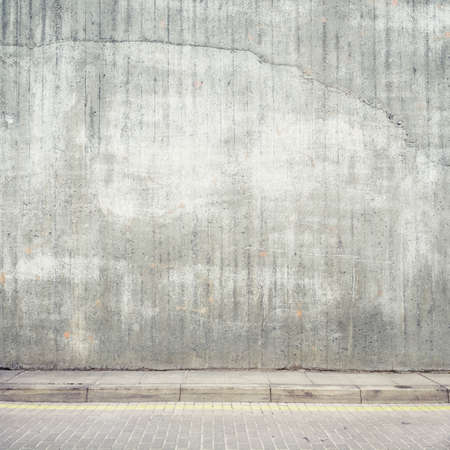 Urban background. Grunge obsolete concrete wall and pavement.