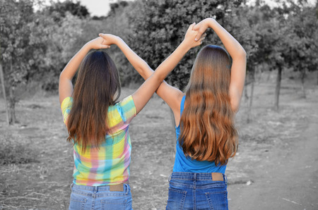 Photo pour Best Friends Forever - two 12 year old teenage girls  holding hands in an infinity forever sign to signify BFF - color over black and white for strong subject focus - image libre de droit