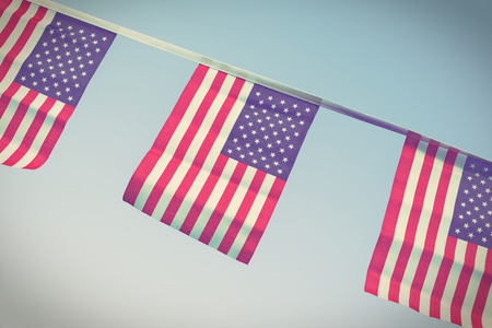 A chain / garland/ bunting of USA flags hanging proudly for July 4 Independence Day - vintage / retro / Instagram processed