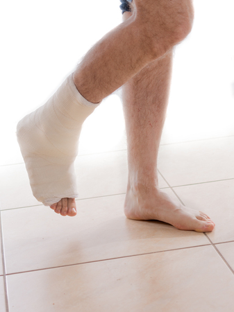 Young man with a broken ankle and a white cast on his leg, walking on crutches (isolated on white)