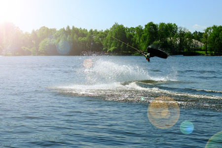 Athlete-wakeboarder performs a jump with a somersault in the air. In the sunlight.