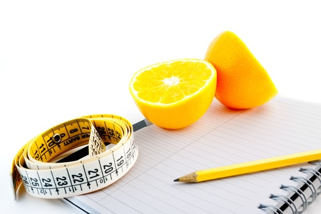 Photo for detail an orange with a measuring tape on notepad - Royalty Free Image