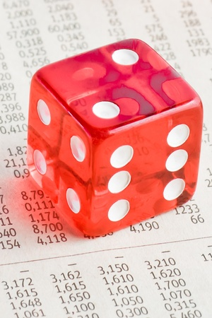 detail of one red dice on the financial newspaper