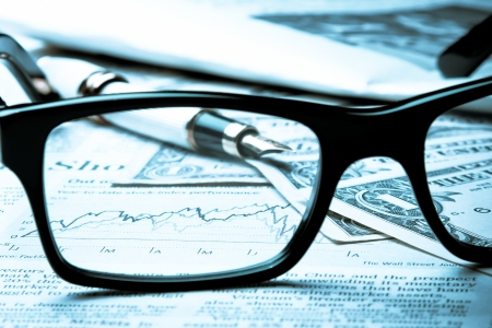 financial chart near dollars seen by unfocused glasses