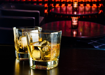 whiskey glasses with ice in a lounge bar on wood table