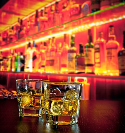 glasses of whiskey with ice on bar table near whiskey bottle on warm atmosphere lounge bar concept