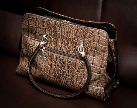 leather handbag from crocodile leather on a brown leather couch
