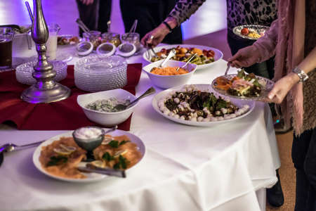 People group catering buffet at a food table. Luxury restaurant with meat, bread and different salad