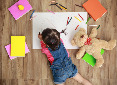 Photo pour Little Asian girl drawing in paper on floor indoors, top view of child on floor - image libre de droit