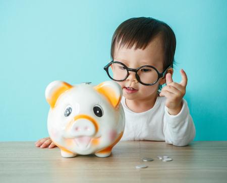 Foto de little baby moneybox putting a coin into a piggy bank - kid saving money for future concept - Imagen libre de derechos