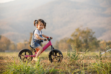 Happy child riding a bike. Little girl on a pink bicycle. Healthy preschool children summer activity. Kids playing outside. Little girl learns 