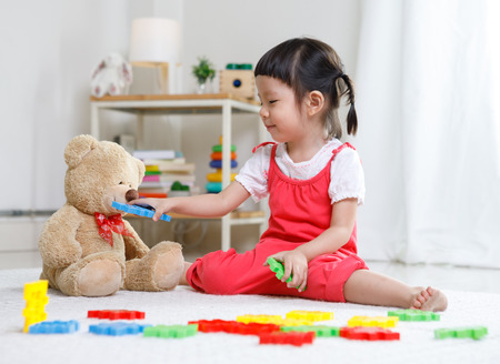 Foto de Preschooler girl learns at school. Cute child playing with teddy bear. Little girl having fun indoors at home, kindergarten or  day care. Educational concept for school kids. - Imagen libre de derechos