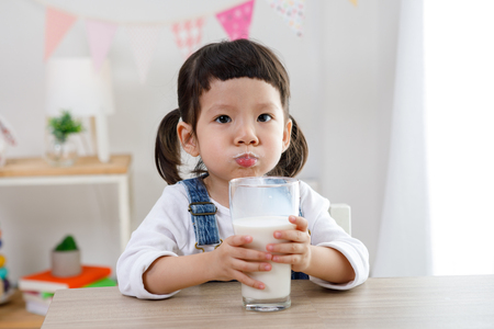 Photo pour Adorable baby girl with dringking milk with milk mustache holding glass of milk - image libre de droit