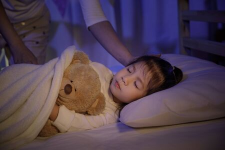 Foto de Mother putting blanket on and stroking head for her little girl daughter on bed in a dark bedroom at night, Child asian girl hug teddy bear, Comfortable children at home concept - Imagen libre de derechos