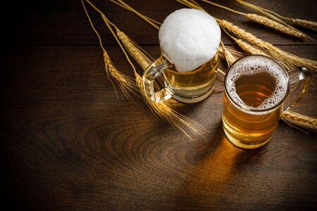 Foto de Glasses of Light Beer with wheat on the wooden table, copy space for your text - Imagen libre de derechos
