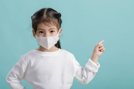 Photo pour Asian little child girl wearing respirator mask to protect coronavirus outbreak and pointing hand to blank background, New virus Covid-19 from   concept, Empty space isolated on blue background - image libre de droit