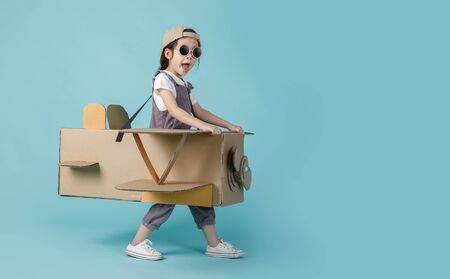 Photo pour Asian little child girl playing with cardboard toy airplane handicraft isolated on blue long banner with copy space for your text, Creative with family and dreaming of flying concept - image libre de droit