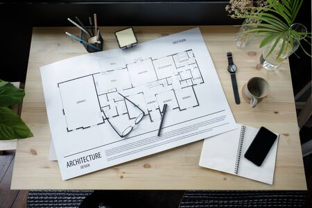 Photo pour Top view workspace mockup of architectural project with architectural project plan, engineering tools, office supplies and hot coffee cup on wooden desk empty space - image libre de droit
