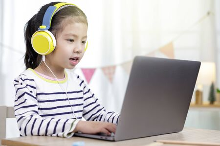 Foto de Asian little child girl learning at home with laptop computer using meeting online app, Quarantine isolation during the Coronavirus (COVID-19) health care, online education concept - Imagen libre de derechos