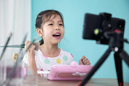 Photo for Happy little Asian girl beauty blogger live video streaming and teaching to use cosmetic make up for kids. - Royalty Free Image