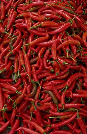 lots of fresh large red spicy chillis shot from overhead at outdoors market in kota kinabalu malatsian borneo