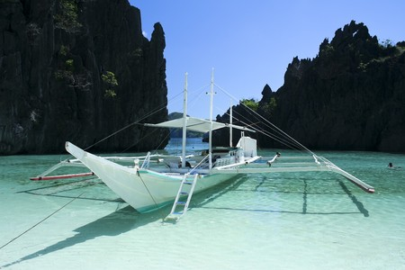 traditional filipino banka outrigger boat surrounded by karst rock formations in clear blue waters of el nido palawan island in the philippines