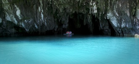 small boat of tourists in the entrance to the underground river in sabang palawan in the philippines