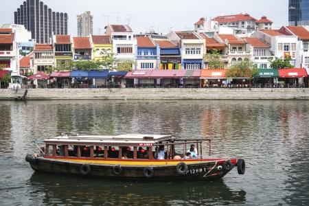 Singapore - May 11, 2008 : Tourist boat passing Clarke Quay.