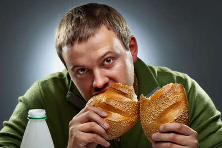Hungry man with mouth full of bread