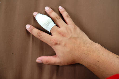 Finger injury with bandage on brown background