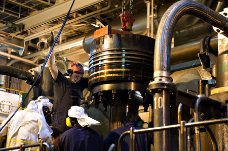 Photo pour Engineers working on large engine of a ship - image libre de droit