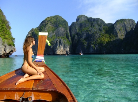 Young woman in bikini sitting on a stern of longtail boat, Phi Phi Lei island, Thailand