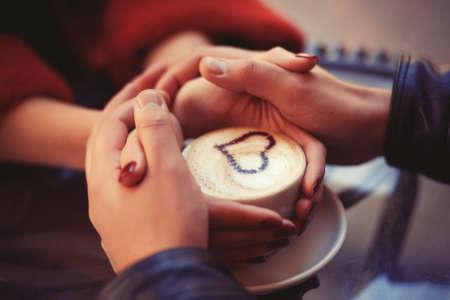 Photo pour Four hands wrapped around a cup - image libre de droit