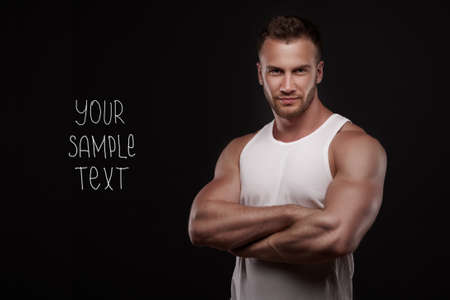 Young handsome  man with  muscular chest with copyspase on dark background