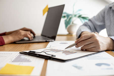 Foto de Two salespeople are working together to prepare a company sales report to bring to the monthly general meeting with the management. Sales management concept. - Imagen libre de derechos