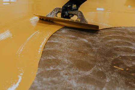 Foto de Worker, coating floor with self-leveling epoxy resin in industrial workshop. - Imagen libre de derechos