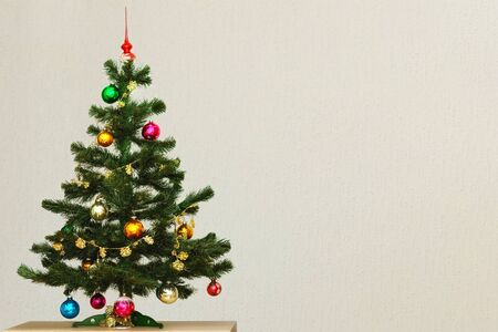 Photo pour Artificial green Christmas tree with colorful Christmas toys, standing on a table against a gray wall. - image libre de droit
