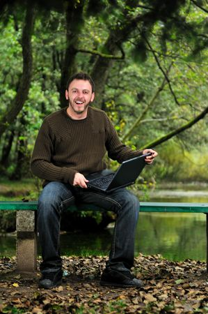one young businessman working on laptop outdoor with green nature in background