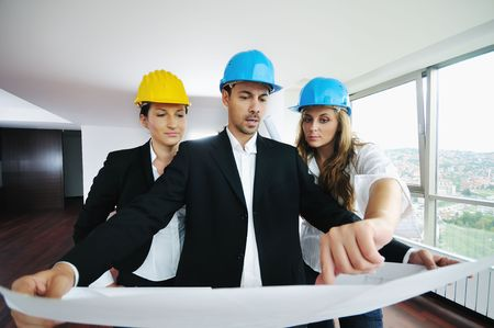 Photo for young arhitect group in big bright modern new apartment looking blueprints and building plans - Royalty Free Image