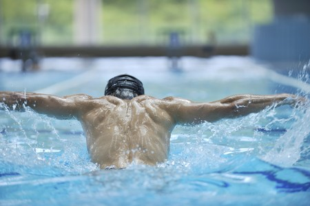 Photo pour young healthy with muscular body man swim on swimming pool and representing healthy and recreation concept - image libre de droit