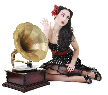 pretty girl listening music on old gramophone isolated on white in studio